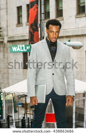 African American Businessman traveling, working in New York. Wearing gray blazer, holding laptop computer, a black man with beard standing on street, tensely looking at you. confident, successful. - stock photo