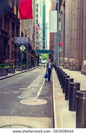 African American Businessman traveling, working in New York. Young black man walking on narrow old street with high buildings, carrying blue bag, wearing blazer. Small car running in far background. - stock photo