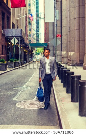 African American Businessman traveling, working in New York. Young black man walking on narrow old street with high buildings, carrying blue bag. Car running on background. Instagram filtered effect.  - stock photo