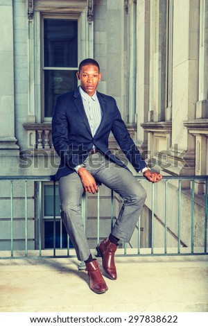 African American businessman working in New York. Wearing black blazer, gray pants, brown leather shoes,  a young guy sitting on railing in vintage style office building, relaxing, Instagram effect.