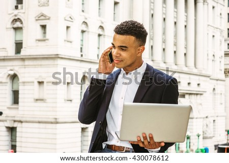 African American Businessman working in New York, wearing black blazer, white shirt, sitting by vintage office building, working on laptop computer, talking on cell phone. Instagram filtered effect.