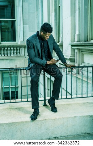 African American Businessman working in New York. Wearing fashionable jacket, necktie, a young guy sitting on railing, looking down, checking messages on cell phone. Filtered look with green tint.