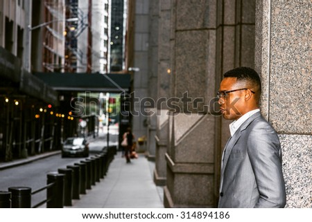 African American Businessman Working in New York. Wearing gray blazer, glasses, a black college student standing on street, sad, thinking, lost in thought. A car driving on narrow road on background.  - stock photo