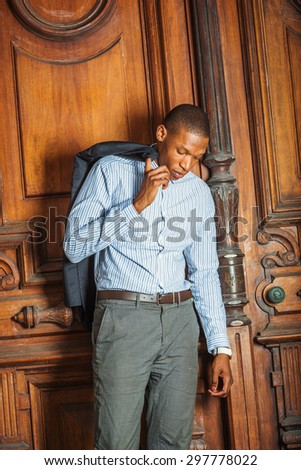African American businessman working in New York. Wearing striped shirt, hand hooking jacket on shoulder, a black teacher standing by vintage style library door way, lowering head, tired, thinking. - stock photo