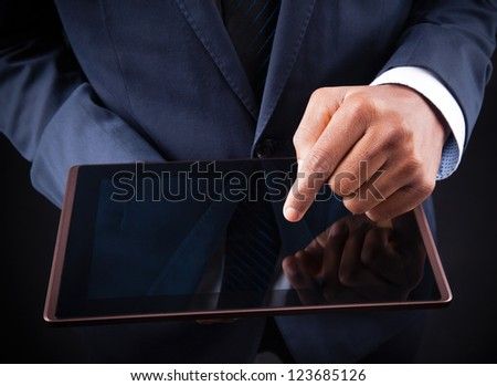 African American businessman working on a digital tablet - stock photo