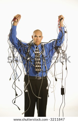 African American businessman wrapped in computer cables. - stock photo
