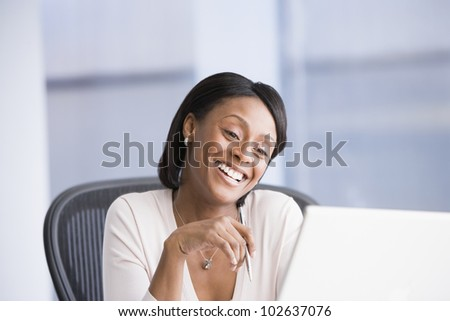 African American businesswoman smiling at laptop - stock photo
