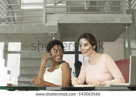 African American businesswoman using mobile phone while female colleague writing on notepad in office - stock photo