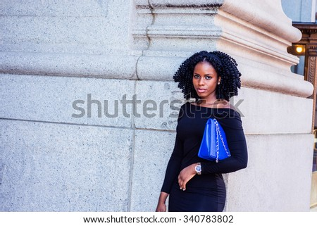 African American Businesswoman working in New York. Wearing long sleeve, slim off shoulder dress, carrying blue bag under arm, a young black lady standing on street. Filtered look with purple tint. - stock photo
