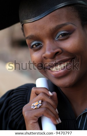 African American college student graduating with mortarboard and diploma or scroll - stock photo