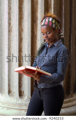 African American college student reading book in front of classical library pillar - stock photo