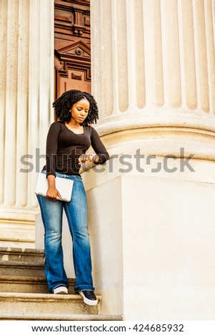 African American college student studying in New York. Holding laptop computer, looking down at wristwatch, a girl standing by column on campus, waiting for you. Time is money. Retro filtered look.