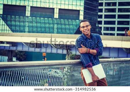 African American college student studying in New York. Wearing blue shirt, glasses, bracelets, holding laptop computer, a young black man standing in business district with high buildings, smiling.  - stock photo