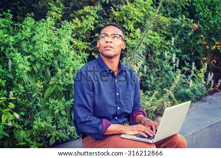 African American college student studying in New York. Wearing glasses, young man sitting by green plants on campus, working on laptop computer, looking up, thinking, hoping, wishing, imagination.  - stock photo