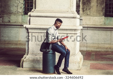 African American College Student studying in New York. Wearing gray shirt, jeans, cloth shoes, carrying shoulder leather bag, a black man sitting on metal pillar on street, relaxing, reading red book.