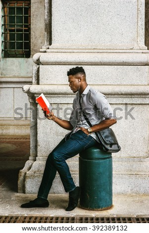 African American College Student studying in New York, wearing gray shirt, jeans, cloth shoes, carrying shoulder leather bag, sitting onl pillar on street, reading red book. Instagram filtered effect.