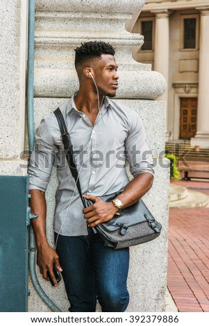African American college student studying in New York, wearing gray shirt, jeans, wristwatch, carrying shoulder leather bag, standing in corner of street, listening music with earphone and cell phone. - stock photo