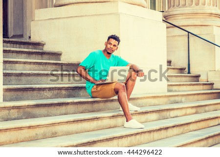 African American college student studying in New York, wearing green V neck T shirt, yellow brown shorts, white sneakers, sitting on stairs of office building on campus, working on laptop computer.  - stock photo