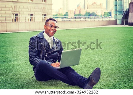 African American college student studying in New York. Wearing leather jacket, jeans, leather shoes, glasses, a young black man sitting on green lawn on campus, working on laptop computer, smiling.  - stock photo