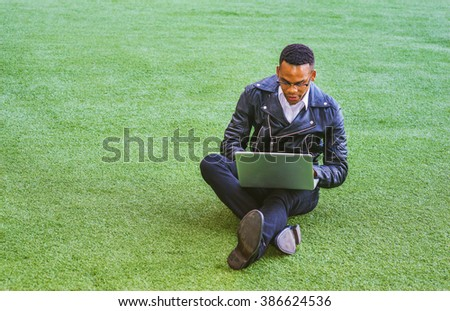 African American college student studying in New York, wearing leather jacket, jeans, shoes, glasses, sitting on green lawn on campus, working on laptop computer, reading, typing, thinking.  - stock photo
