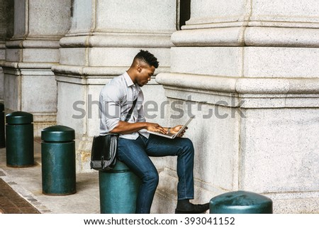 African American College Student studying in New York, wearing shirt, jeans, carrying shoulder leather bag, sitting on pillar on street, reading, working on laptop computer. Instagram filtered effect. - stock photo