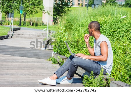 African American College Student studying in New York, wearing T shirt, black jeans, white sneakers,, sitting on wooden road on campus, working on laptop computer, thinking. Color filtered effect
