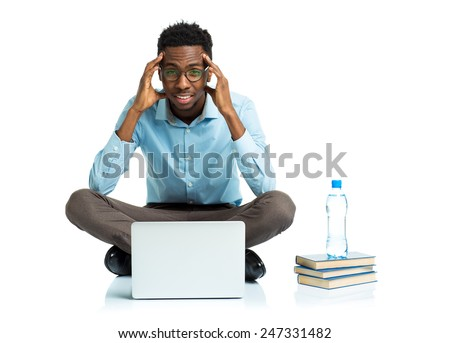 African american college student with headache sitting on white background with laptop and some books - stock photo