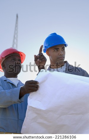 African American construction workers with blueprints - stock photo