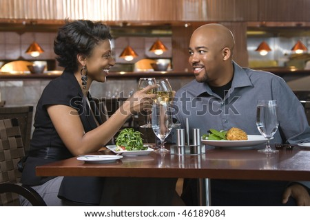African-American couple dining out. They are toasting with glasses of white wine and smiling. Horizontal shot. - stock photo