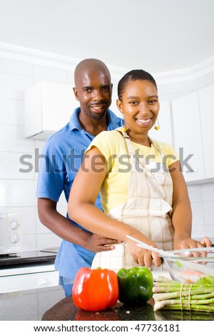 african american couple hugging in kitchen - stock photo