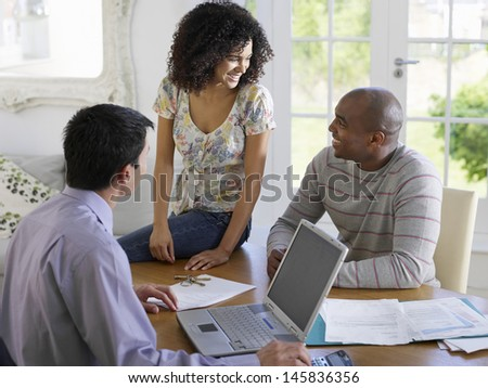 African American couple sitting at dining table with financial advisor - stock photo