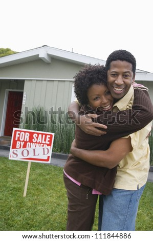 African American couple standing in front of their house