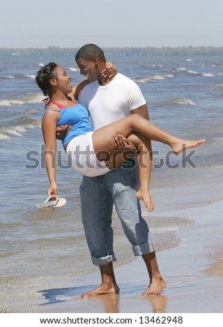 African American couple together on the beach near the ocean with man picking up wife