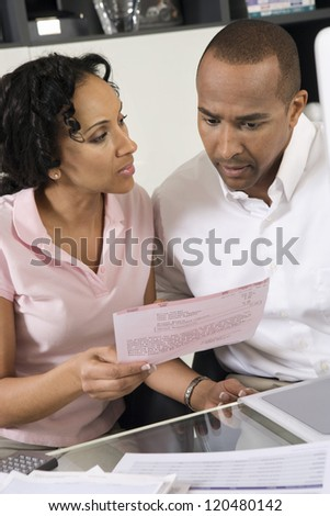 African American couple worried over excess domestic bill - stock photo