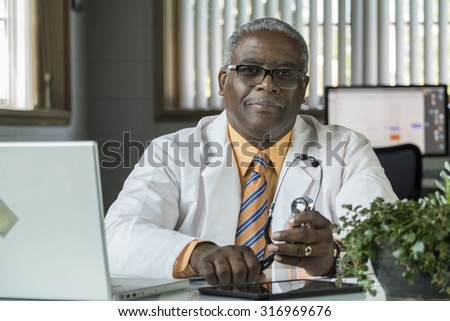 African American Doctor sitting in his desk with a laptop - stock photo