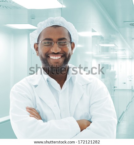 African American doctor with white uniforms in modern facility smiling - stock photo