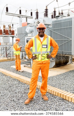 african american electrical technician with colleague on background in substation - stock photo