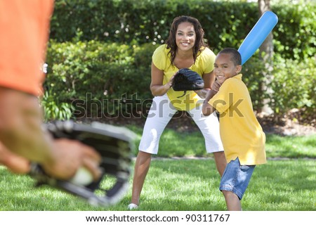 African American family, man, woman, boy child, mother, father, son playing baseball together outside. - stock photo