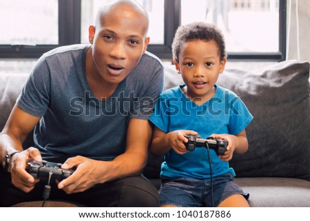 African American family of father and son at home sitting in sofa couch and playing console video games together.