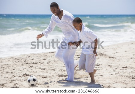 African American family of father and son, man & boy child, having fun playing football soccer in the sand on a sunny beach - stock photo