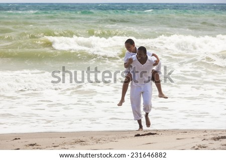 African American family of father and son, man & boy child, playing piggy back and having fun in the sand and waves on a sunny beach - stock photo