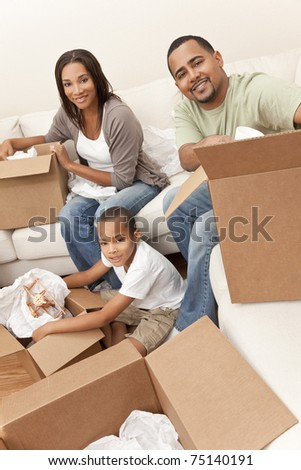 African American family, parents and son, unpacking boxes and moving into a new home, The adults are unpacking crockery and homeware, the child is unpacking a toy airplane. - stock photo