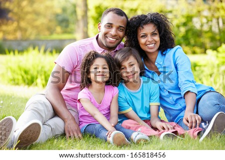 African American Family Sitting In Garden - stock photo