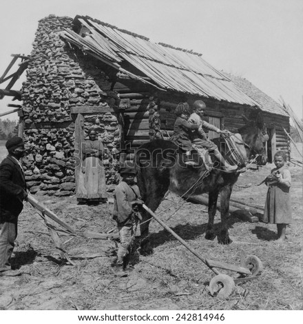 African American farm family outside their log cabin home in North Carolina. Rural poverty persisted for several decades following abrupt emancipation of slaves in a post-Civil War South. Ca. 1903. - stock photo