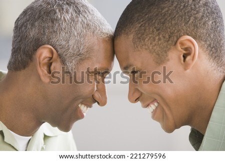 African American father and adult son touching foreheads - stock photo