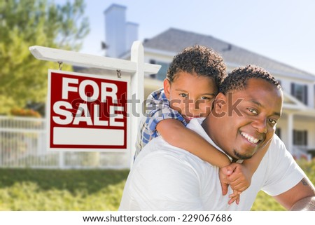 African American Father and Mixed Race Son In Front of Home For Sale Real Estate Sign and New House. - stock photo