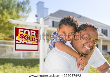African American Father and Mixed Race Son In Front of Sold Home For Sale Real Estate Sign and New House. - stock photo