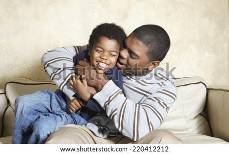 African American father and young son playing on sofa - stock photo