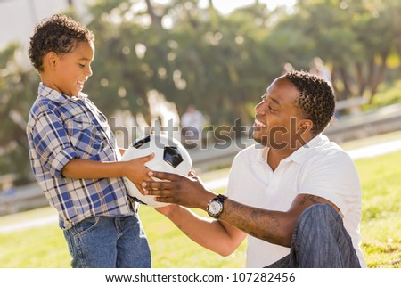 African American Father Hands New Soccer Ball to Mixed Race Son at the Park. - stock photo