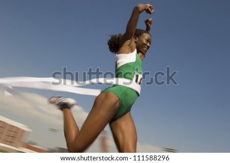 African American female athlete crossing finish line in race - stock photo